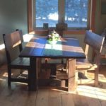 Farmhouse pedestal dingin table constructed with a timberframe design